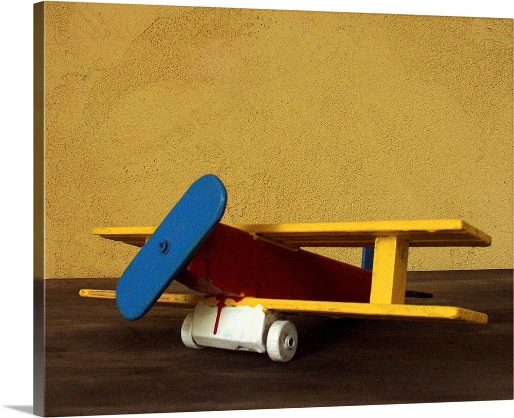Large Solid-Faced Canvas Print Wall Art Print 30 x 24 entitled Toy wooden airplane Solid-Faced Canvas Print entitled Toy wooden airplane.  Multiple sizes available.  Primary colors within this image include Dark Red, Brown, Light Yellow, Muted Blue.  Made in the USA.  All products come with a 365 day workmanship guarantee.  Inks used are latex-based and designed to last.  Archival inks prevent fading and preserve as much fine detail as possible with no over-saturation or color shifting.  Featuring a proprietary design, our canvases produce the tightest corners without any bubbles, ripples, or bumps and will not warp or sag over time.