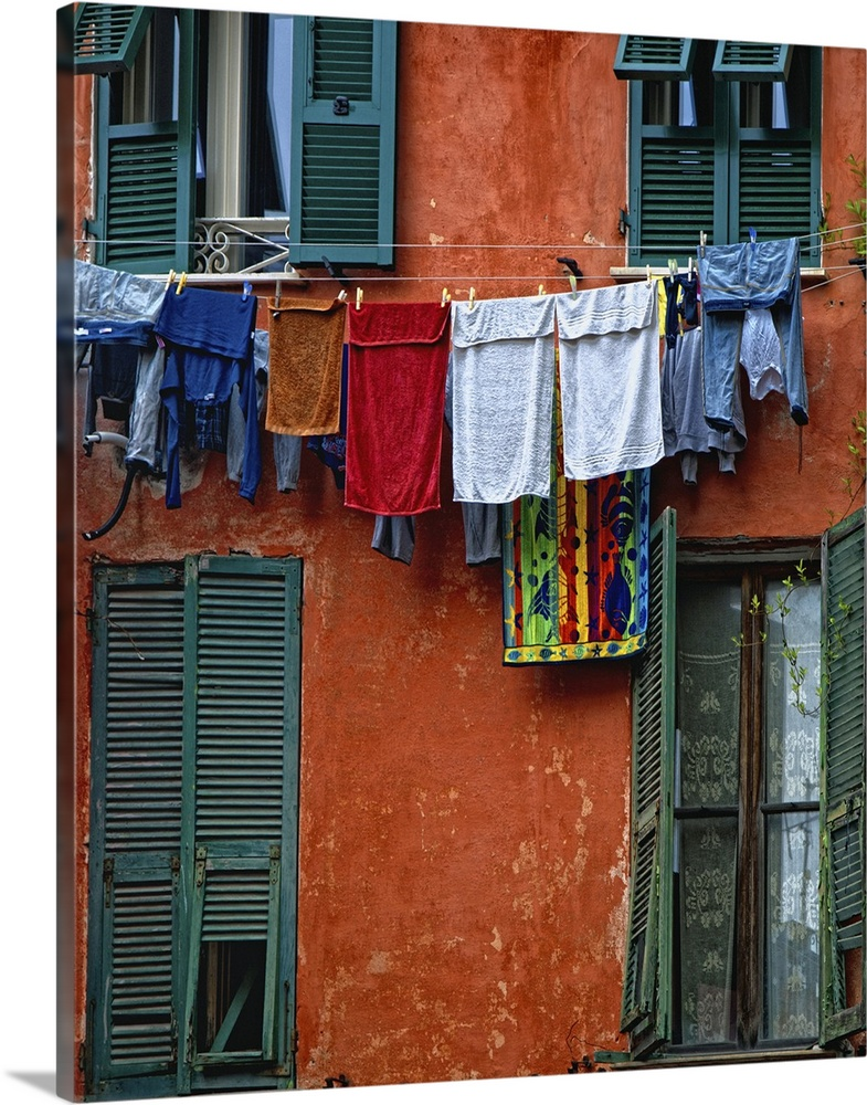 Large Gallery-Wrapped Canvas Wall Art Print 16 x 20 entitled Washed clothes on the clothesline drying, Monterosso Gallery-Wrapped Canvas entitled Washed clothes on the clothesline drying, Monterosso.  Ropa tendida. Pared color. Monterosso.  Multiple sizes available.  Primary colors within this image include Dark Red, Dark Blue, Black, Pale Blue.  Made in USA.  All products come with a 365 day workmanship guarantee.  Archival-quality UV-resistant inks.  Canvas frames are built with farmed or reclaimed domestic pine or poplar wood.  Canvases have a UVB protection built in to protect against fading and moisture and are designed to last for over 100 years.