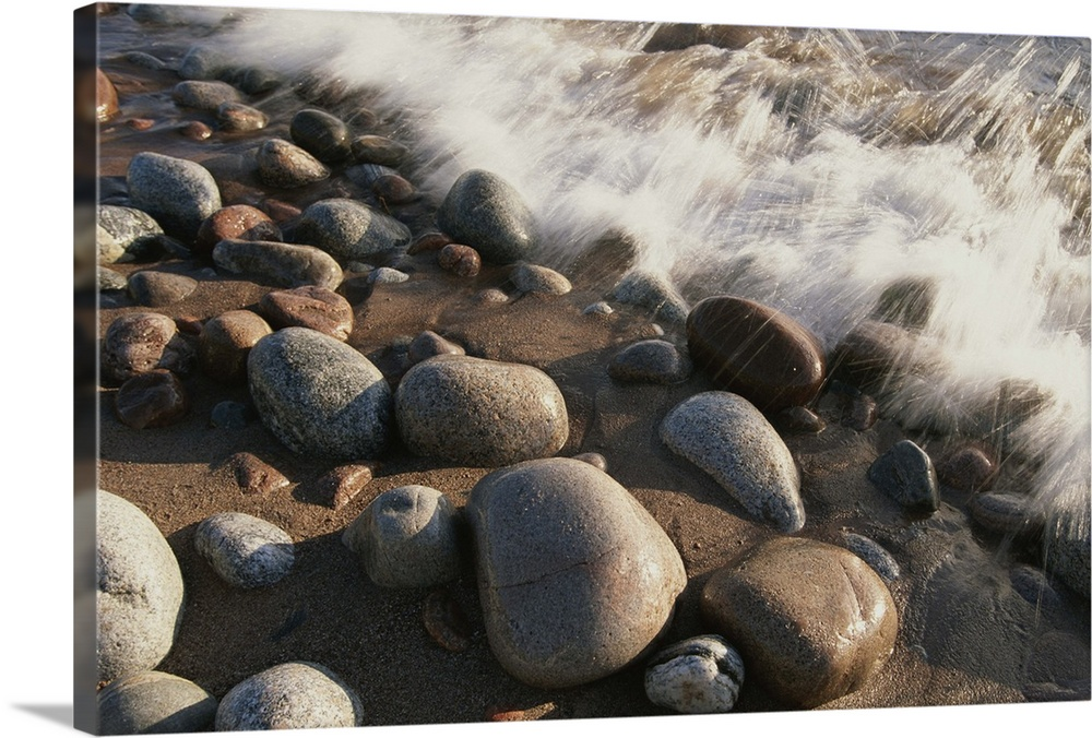 Large Solid-Faced Canvas Print Wall Art Print 30 x 20 entitled A close view time exposure of surf washing over stones on t... Solid-Faced Canvas Print entitled A close view time exposure of surf washing over stones on the beach.  A close view time exposure of surf washing over stones on the beach.  Multiple sizes available.  Primary colors within this image include Brown, Dark Gray, Silver.  Made in the USA.  Satisfaction guaranteed.  Archival-quality UV-resistant inks.  Canvas is handcrafted and made-to-order in the United States using high quality artist-grade canvas.  Featuring a proprietary design, our canvases produce the tightest corners without any bubbles, ripples, or bumps and will not warp or sag over time.