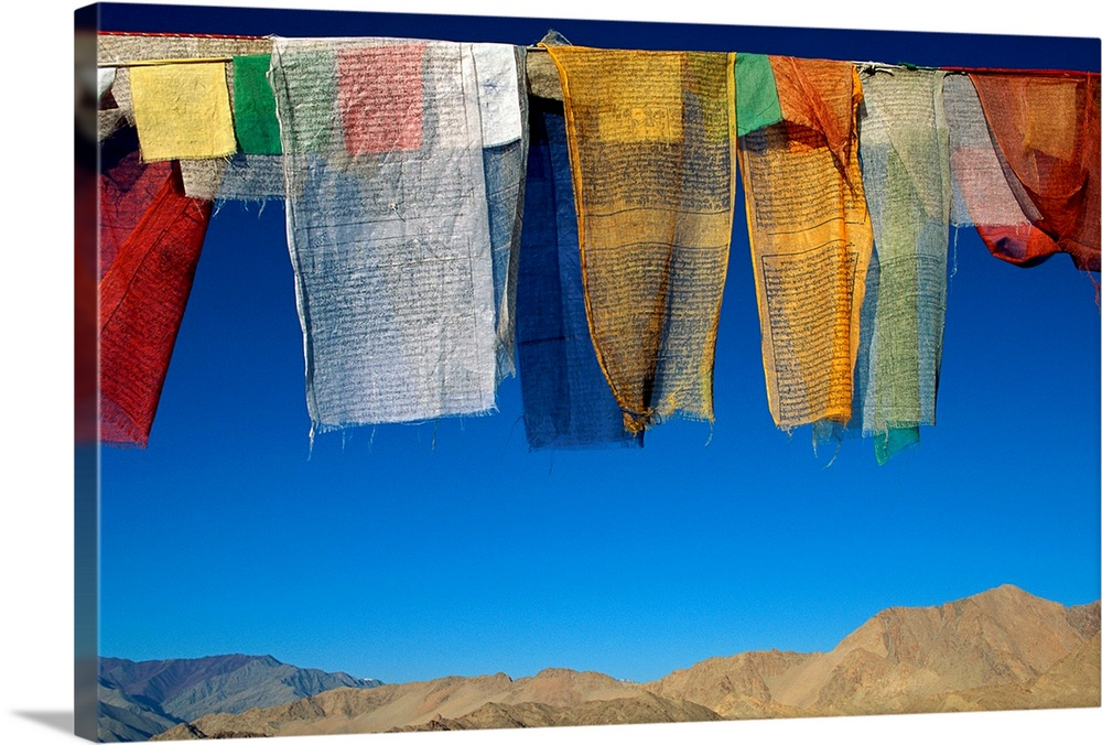 Large Gallery-Wrapped Canvas Wall Art Print 24 x 16 entitled A line of multi colored prayer flags sway in the gentle breez... Gallery-Wrapped Canvas entitled A line of multi colored prayer flags sway in the gentle breeze in Ladakh.  A line of colorful cloths are photographed hanging from a clothes line with a view of mountainous terrain just below them.  Multiple sizes available.  Primary colors within this image include Dark Red, Gray, Royal Blue, Dark Navy Blue.  Made in the USA.  Satisfaction guaranteed.  Archival-quality UV-resistant inks.  Museum-quality, artist-grade canvas mounted on sturdy wooden stretcher bars 1.5 thick.  Comes ready to hang.  Canvas is designed to prevent fading.