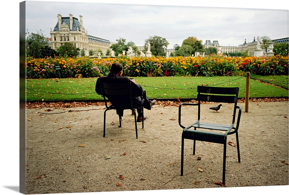 Large Solid-Faced Canvas Print Wall Art Print 30 x 20 entitled A man reads in the Tuileries Gardens The Louvre is in the b... Solid-Faced Canvas Print entitled A man reads in the Tuileries Gardens The Louvre is in the background.  Paris, France.  Multiple sizes available.  Primary colors within this image include Brown, Forest Green, Black, White.  Made in the USA.  Satisfaction guaranteed.  Inks used are latex-based and designed to last.  Canvas depth is 1.25 and includes a finished backing with pre-installed hanging hardware.  Canvas is handcrafted and made-to-order in the United States using high quality artist-grade canvas.