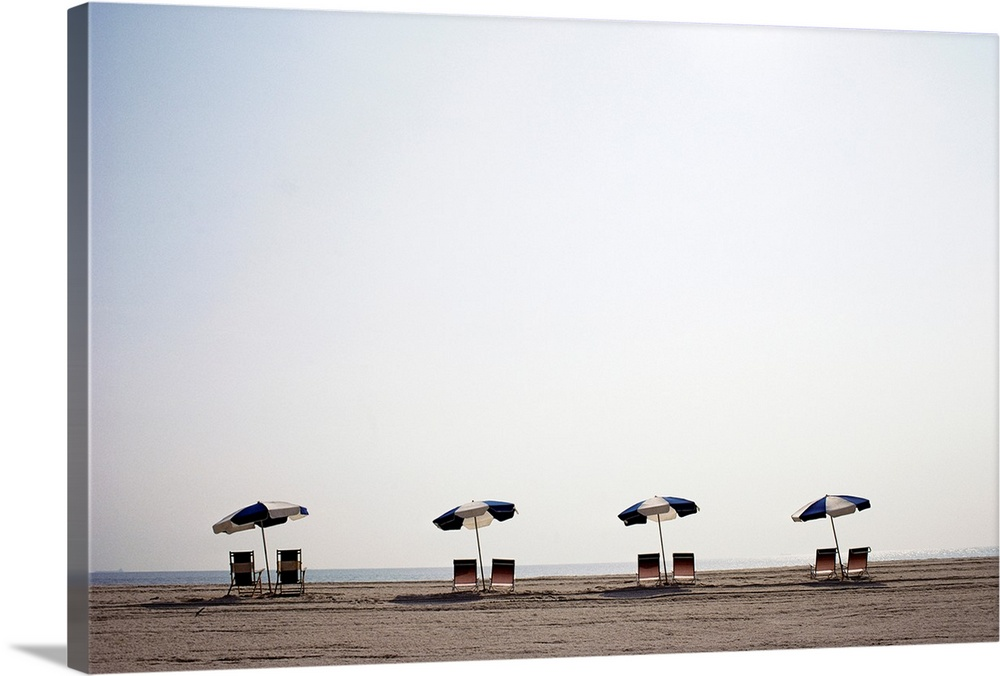 Large Solid-Faced Canvas Print Wall Art Print 30 x 20 entitled A row of empty chairs, empty sand, and solitary umbrellas a... Solid-Faced Canvas Print entitled A row of empty chairs, empty sand, and solitary umbrellas at Cape Henlopen State Park.  From the National Geographic Collection.  Photograph of beach chairs and parasols on the beach.  Multiple sizes available.  Primary colors within this image include Black, Gray, White.  Made in the USA.  All products come with a 365 day workmanship guarantee.  Inks used are latex-based and designed to last.  Canvas is handcrafted and made-to-order in the United States using high quality artist-grade canvas.  Archival inks prevent fading and preserve as much fine detail as possible with no over-saturation or color shifting.