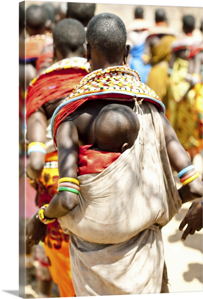 Large Gallery-Wrapped Canvas Wall Art Print 16 x 24 entitled A Samburu baby rests on his mother as she dances with others Gallery-Wrapped Canvas entitled A Samburu baby rests on his mother as she dances with others.  A Samburu baby rests on his mother as she dances with others.  Multiple sizes available.  Primary colors within this image include Orange Yellow Black White.  Made in the USA.  All products come with a 365 day workmanship guarantee.  Inks used are latex-based and designed to last.  Museum-quality artist-grade canvas mounted on sturdy wooden stretcher bars 1.5 thick.  Comes ready to hang.  Canvases are stretched across a 1.5 inch thick wooden frame with easy-to-mount hanging hardware.