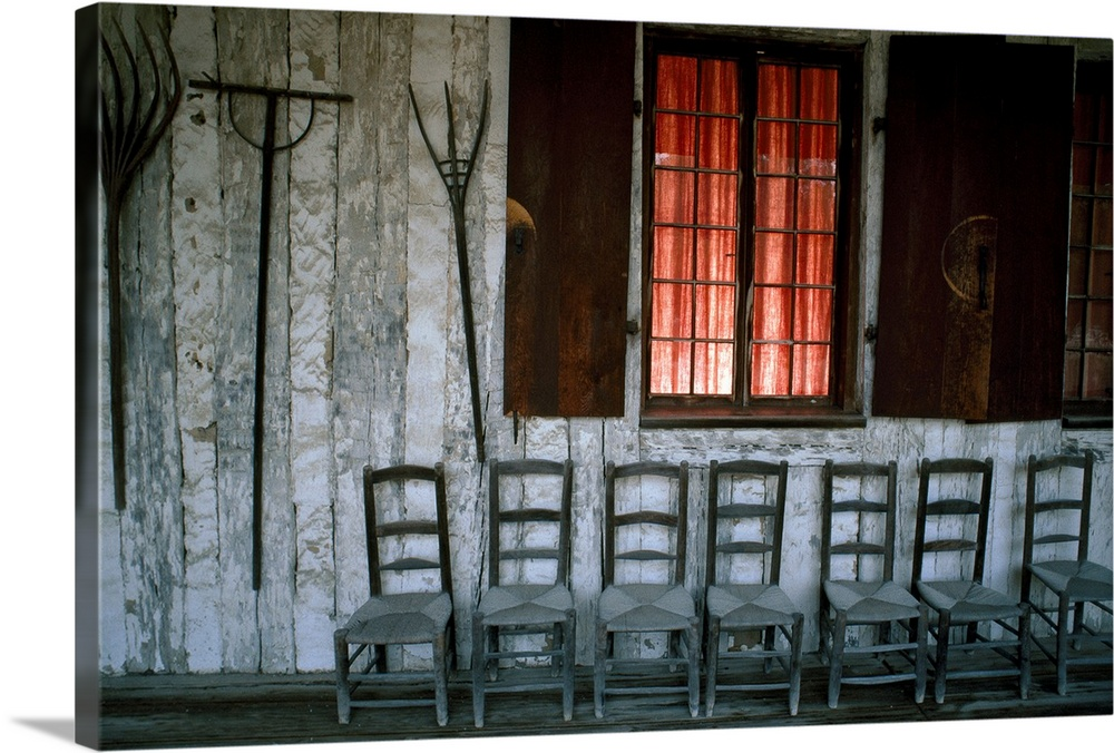 Large Solid-Faced Canvas Print Wall Art Print 30 x 20 entitled Porch of the Bolduc House Museum with antique chairs and ra... Solid-Faced Canvas Print entitled Porch of the Bolduc House Museum with antique chairs and rakes, Missouri.  Large canvas photo of an old deck with wooden chairs underneath a window outside and rakes hanging on the wall.  Multiple sizes available.  Primary colors within this image include Dark Red, Pink, Black, Gray.  Made in the USA.  Satisfaction guaranteed.  Archival-quality UV-resistant inks.  Featuring a proprietary design, our canvases produce the tightest corners without any bubbles, ripples, or bumps and will not warp or sag over time.  Canvas is handcrafted and made-to-order in the United States using high quality artist-grade canvas.