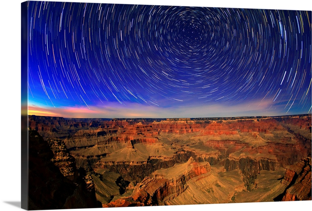 Large Solid-Faced Canvas Print Wall Art Print 30 x 20 entitled Star trails in the evening sky Solid-Faced Canvas Print entitled Star trails in the evening sky.  Star trails in the evening sky, and sedimentary rock ranging in age from 200 million to 2 billion years old, in bright moonlight. With a camera on a tripod, as the Earth turns, stars make arcs in the sky. The arcs are centered on the north celestial pole.  Multiple sizes available.  Primary colors within this image include Blue, Brown, Dark Blue, Black.  Made in the USA.  All products come with a 365 day workmanship guarantee.  Inks used are latex-based and designed to last.  Canvas depth is 1.25 and includes a finished backing with pre-installed hanging hardware.  Canvas is handcrafted and made-to-order in the United States using high quality artist-grade canvas.