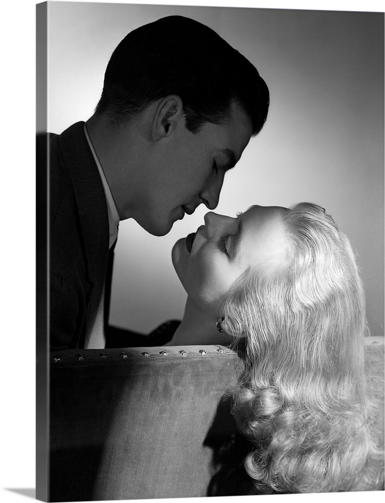 Large Solid-Faced Canvas Print Wall Art Print 30 x 40 entitled 1940s 1950s Movie Star Studio Style Romantic Couple Embraci... Solid-Faced Canvas Print entitled 1940s 1950s Movie Star Studio Style Romantic Couple Embracing On Sofa About To Kiss.  1940s 1950s Movie Star Studio Style Romantic Couple Embracing On Sofa About To Kiss.  Multiple sizes available.  Primary colors within this image include Black, Silver.  Made in USA.  All products come with a 365 day workmanship guarantee.  Inks used are latex-based and designed to last.  Canvas depth is 1.25 and includes a finished backing with pre-installed hanging hardware.  Archival inks prevent fading and preserve as much fine detail as possible with no over-saturation or color shifting.