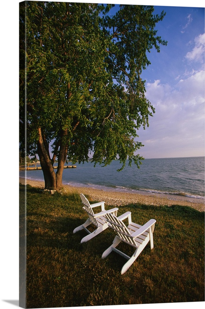 Large Solid-Faced Canvas Print Wall Art Print 20 x 30 entitled Adirondack Chairs Solid-Faced Canvas Print entitled Adirondack Chairs.  Tall print on canvas of two chairs sitting on grass facing the water with a tree next to them.  Multiple sizes available.  Primary colors within this image include Brown, Sky Blue, Muted Blue, Dark Forest Green.  Made in USA.  All products come with a 365 day workmanship guarantee.  Archival-quality UV-resistant inks.  Canvas is handcrafted and made-to-order in the United States using high quality artist-grade canvas.  Featuring a proprietary design, our canvases produce the tightest corners without any bubbles, ripples, or bumps and will not warp or sag over time.