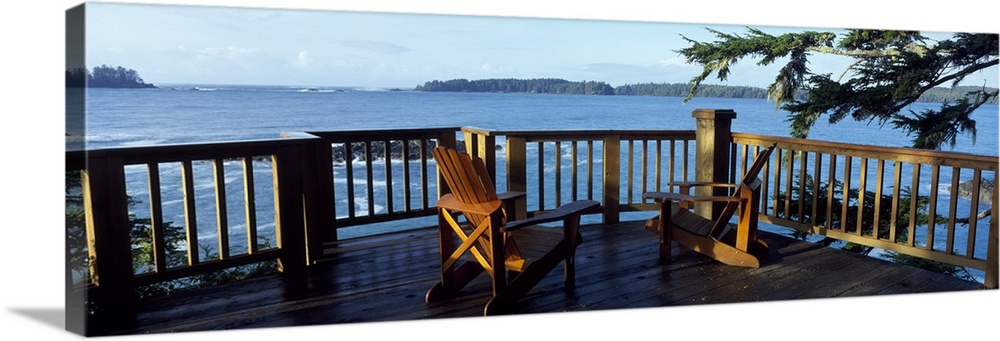 Large Solid-Faced Canvas Print Wall Art Print 48 x 16 entitled Adirondack Chairs Middle Beach Lodge Vancouver BC Solid-Faced Canvas Print entitled Adirondack Chairs Middle Beach Lodge Vancouver BC.  Two chairs sit on a raised deck overlooking a large body of water.  Multiple sizes available.  Primary colors within this image include Black, Gray, Muted Blue, Pale Blue.  Made in the USA.  All products come with a 365 day workmanship guarantee.  Archival-quality UV-resistant inks.  Archival inks prevent fading and preserve as much fine detail as possible with no over-saturation or color shifting.  Canvas depth is 1.25 and includes a finished backing with pre-installed hanging hardware.