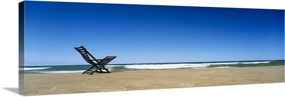 Large Solid-Faced Canvas Print Wall Art Print 48 x 16 entitled Beach Chair Grand Haven MI Solid-Faced Canvas Print entitled Beach Chair Grand Haven MI.  Huge panoramic piece of a lone beach chair skewed to the left sitting in the sand with waves crashing and a clear blue sky above.  Multiple sizes available.  Primary colors within this image include Sky Blue, Black, Light Gray, Muted Blue.  Made in USA.  All products come with a 365 day workmanship guarantee.  Inks used are latex-based and designed to last.  Archival inks prevent fading and preserve as much fine detail as possible with no over-saturation or color shifting.  Canvas is handcrafted and made-to-order in the United States using high quality artist-grade canvas.
