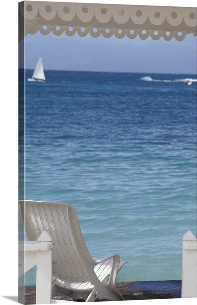 Large Solid-Faced Canvas Print Wall Art Print 20 x 30 entitled Beach Chair Overlooking Ocean Guadeloupe Caribbean Solid-Faced Canvas Print entitled Beach Chair Overlooking Ocean Guadeloupe Caribbean.  Oversized, portrait photograph of beach chair beneath a canopy, looking toward clear blue ocean waters, in Guadeloupe, Caribbean.  Multiple sizes available.  Primary colors within this image include Sky Blue, Dark Gray.  Made in the USA.  All products come with a 365 day workmanship guarantee.  Archival-quality UV-resistant inks.  Canvas depth is 1.25 and includes a finished backing with pre-installed hanging hardware.  Canvas is handcrafted and made-to-order in the United States using high quality artist-grade canvas.