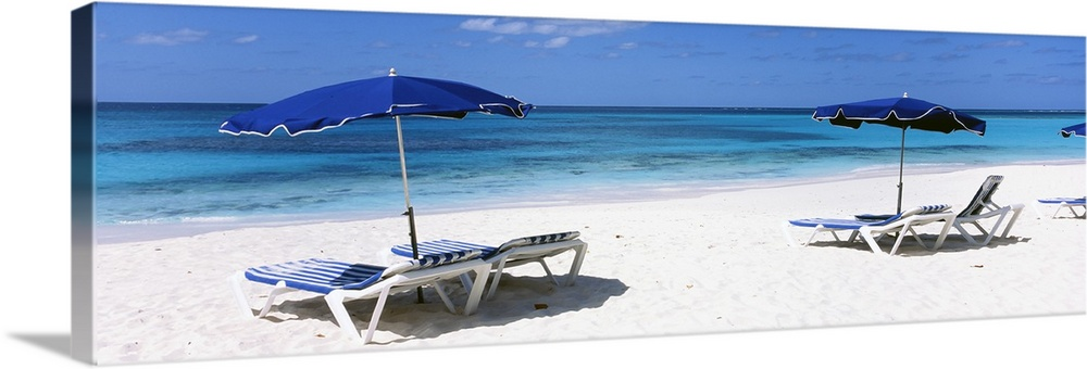 Large Solid-Faced Canvas Print Wall Art Print 48 x 16 entitled Beach chairs with beach umbrellas on the beach, Shoal Bay B... Solid-Faced Canvas Print entitled Beach chairs with beach umbrellas on the beach, Shoal Bay Beach, Anguilla.  Beach chairs and umbrellas are pictured in panoramic view along the beach and close to the ocean.  Multiple sizes available.  Primary colors within this image include Dark Blue, Light Gray, White, Royal Blue.  Made in USA.  Satisfaction guaranteed.  Inks used are latex-based and designed to last.  Canvas is handcrafted and made-to-order in the United States using high quality artist-grade canvas.  Archival inks prevent fading and preserve as much fine detail as possible with no over-saturation or color shifting.