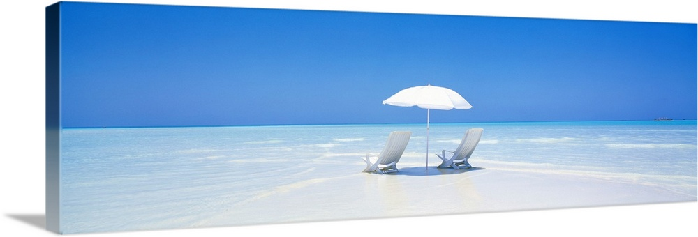 Large Solid-Faced Canvas Print Wall Art Print 48 x 16 entitled Beach Parasol & Chairs Maldives Solid-Faced Canvas Print entitled Beach Parasol  Chairs Maldives .  A panoramic photograph displaying two chairs sitting underneath an umbrella on a sandy beach in Maldives.  The clear water of the ocean sparkles in the sun.  Multiple sizes available.  Primary colors within this image include Black, White, Royal Blue.  Made in USA.  All products come with a 365 day workmanship guarantee.  Inks used are latex-based and designed to last.  Canvas depth is 1.25 and includes a finished backing with pre-installed hanging hardware.  Featuring a proprietary design, our canvases produce the tightest corners without any bubbles, ripples, or bumps and will not warp or sag over time.