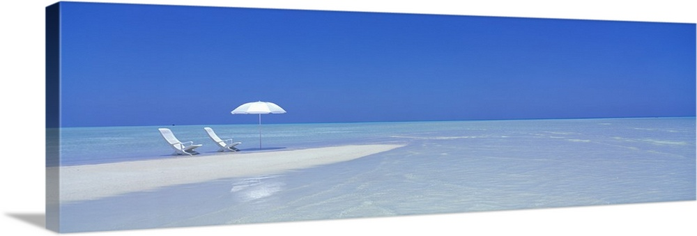 Large Gallery-Wrapped Canvas Wall Art Print 30 x 10 entitled Beach Scene, Digufinolhu, Maldives Gallery-Wrapped Canvas entitled Beach Scene, Digufinolhu, Maldives.  Large panoramic picture of two white chairs and a white beach umbrella sitting on sand that stretches into the crystal clear water.  Multiple sizes available.  Primary colors within this image include Black, Royal Blue, Light Gray Blue.  Made in USA.  Satisfaction guaranteed.  Inks used are latex-based and designed to last.  Canvas frames are built with farmed or reclaimed domestic pine or poplar wood.  Canvas is designed to prevent fading.