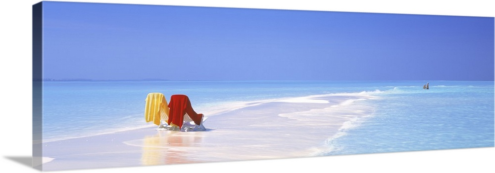 Large Gallery-Wrapped Canvas Wall Art Print 30 x 10 entitled Beach Scenic The Maldives Gallery-Wrapped Canvas entitled Beach Scenic The Maldives.  Two beach chairs sit in the sand surrounded by clean, transparent water in The Maldives. Relaxing, cool tones dominate and meld well with vibrant colored towels on beach chairs.  Multiple sizes available.  Primary colors within this image include Dark Red, Peach, Sky Blue, White.  Made in the USA.  Satisfaction guaranteed.  Inks used are latex-based and designed to last.  Museum-quality, artist-grade canvas mounted on sturdy wooden stretcher bars 1.5 thick.  Comes ready to hang.  Canvas is acid-free and 20 millimeters thick.