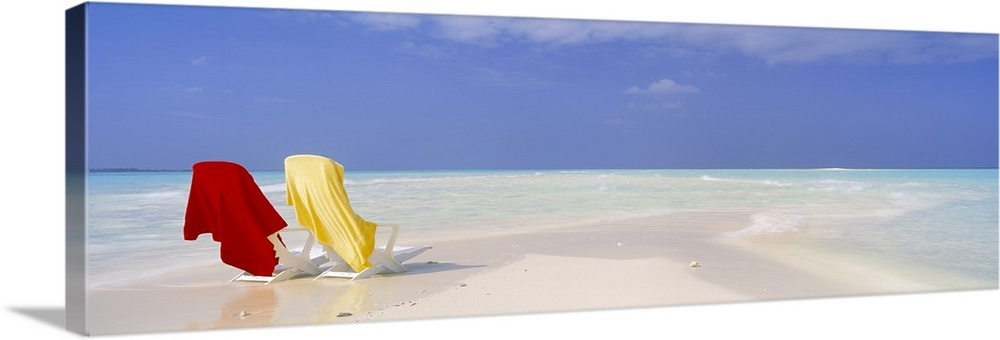 Large Gallery-Wrapped Canvas Wall Art Print 30 x 10 entitled Beach Scenic The Maldives Gallery-Wrapped Canvas entitled Beach Scenic The Maldives.  An image of two beach chairs sitting on a sandbar with clear ocean water washing up on shore nearby on canvas.  Multiple sizes available.  Primary colors within this image include Dark Red, Dark Yellow, Sky Blue, White.  Made in USA.  Satisfaction guaranteed.  Inks used are latex-based and designed to last.  Canvas is designed to prevent fading.  Museum-quality, artist-grade canvas mounted on sturdy wooden stretcher bars 1.5 thick.  Comes ready to hang.