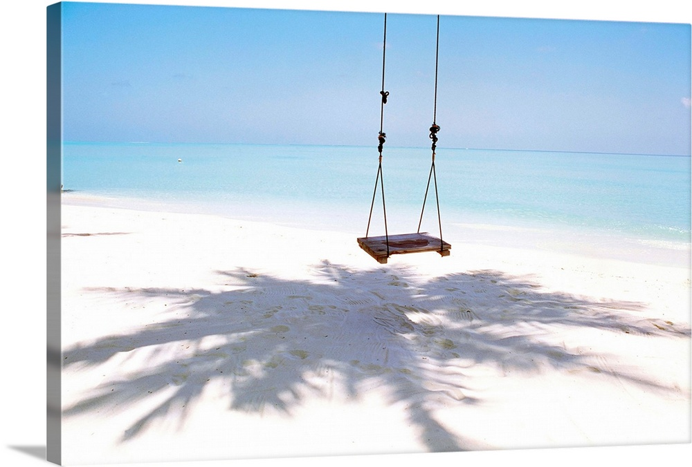 Large Solid-Faced Canvas Print Wall Art Print 30 x 20 entitled Beach swing and shadow of palm tree on sand Solid-Faced Canvas Print entitled Beach swing and shadow of palm tree on sand.  Multiple sizes available.  Primary colors within this image include Sky Blue, Black, White.  Made in USA.  Satisfaction guaranteed.  Archival-quality UV-resistant inks.  Canvas depth is 1.25 and includes a finished backing with pre-installed hanging hardware.  Canvas is handcrafted and made-to-order in the United States using high quality artist-grade canvas.