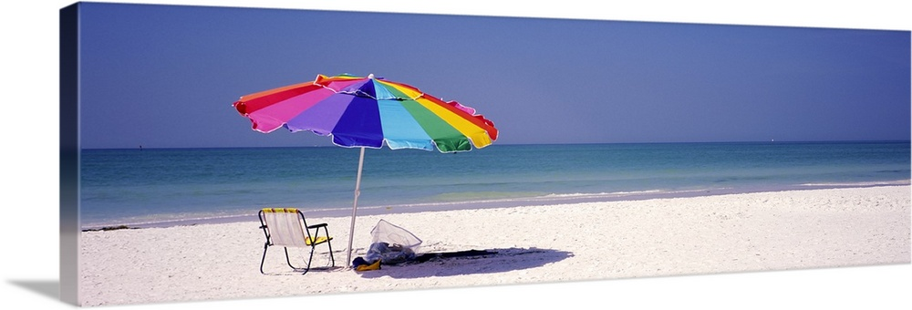 Large Solid-Faced Canvas Print Wall Art Print 48 x 16 entitled Beach umbrella and a folding chair on the beach, Fort De So... Solid-Faced Canvas Print entitled Beach umbrella and a folding chair on the beach, Fort De Soto Park, Tierra Verde, Florida.  Panoramic photograph of beach chair and parasol in the sand, with ocean fading into the distance.  The sky is clear.  Multiple sizes available.  Primary colors within this image include Yellow, Black, White, Royal Blue.  Made in the USA.  Satisfaction guaranteed.  Archival-quality UV-resistant inks.  Canvas depth is 1.25 and includes a finished backing with pre-installed hanging hardware.  Canvas is handcrafted and made-to-order in the United States using high quality artist-grade canvas.