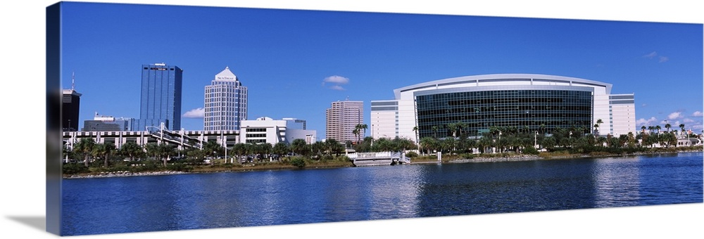 Large Solid-Faced Canvas Print Wall Art Print 48 x 16 entitled Buildings at the waterfront, St. Pete Times Forum, Tampa, F... Solid-Faced Canvas Print entitled Buildings at the waterfront, St. Pete Times Forum, Tampa, Florida.  Multiple sizes available.  Primary colors within this image include Dark Gray, Silver, Royal Blue.  Made in the USA.  All products come with a 365 day workmanship guarantee.  Archival-quality UV-resistant inks.  Featuring a proprietary design, our canvases produce the tightest corners without any bubbles, ripples, or bumps and will not warp or sag over time.  Archival inks prevent fading and preserve as much fine detail as possible with no over-saturation or color shifting.