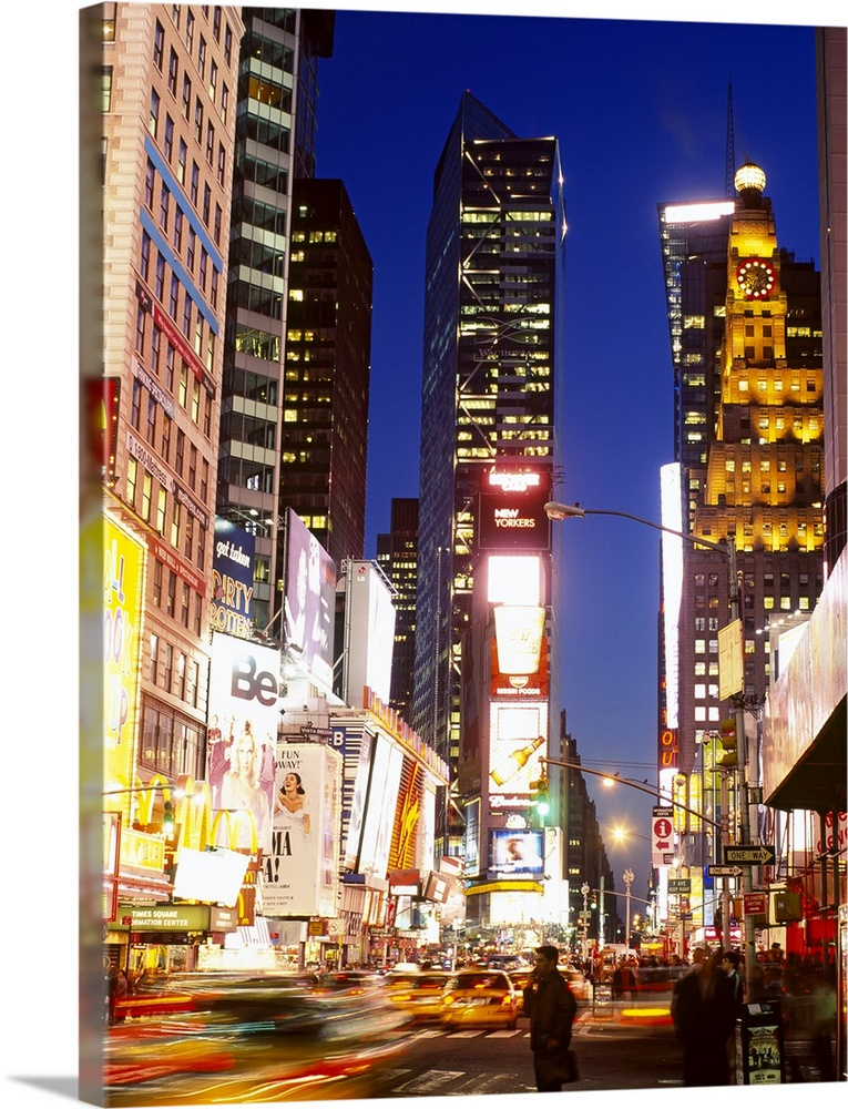 Large Solid-Faced Canvas Print Wall Art Print 30 x 40 entitled Buildings in a city lit up at dusk, Times Square, Manhattan... Solid-Faced Canvas Print entitled Buildings in a city lit up at dusk, Times Square, Manhattan, New York City, New York State.  Times square is illuminated under a night sky as cars appear out of focus as they are in motion.  Multiple sizes available.  Primary colors within this image include Yellow, Dark Blue, Dark Gray, White.  Made in the USA.  Satisfaction guaranteed.  Inks used are latex-based and designed to last.  Canvas depth is 1.25 and includes a finished backing with pre-installed hanging hardware.  Canvas is handcrafted and made-to-order in the United States using high quality artist-grade canvas.