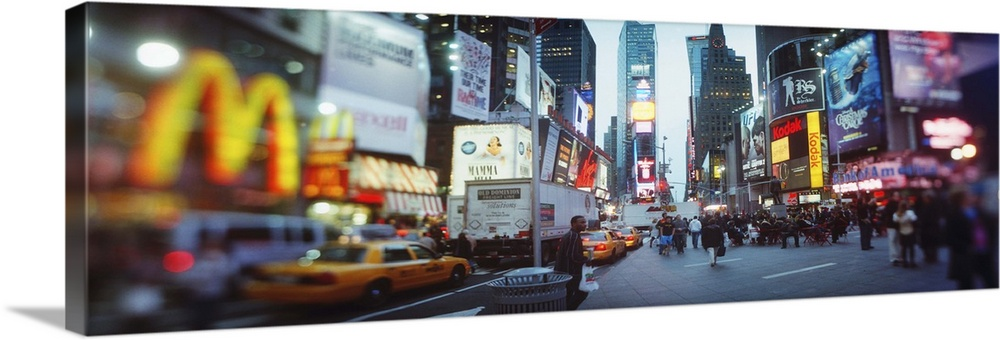 Large Solid-Faced Canvas Print Wall Art Print 48 x 16 entitled Buildings lit up at dusk Times Square Manhattan New York Ci... Solid-Faced Canvas Print entitled Buildings lit up at dusk Times Square Manhattan New York City New York State.  Multiple sizes available.  Primary colors within this image include Light Yellow, Black, Gray, White.  Made in the USA.  Satisfaction guaranteed.  Archival-quality UV-resistant inks.  Featuring a proprietary design, our canvases produce the tightest corners without any bubbles, ripples, or bumps and will not warp or sag over time.  Canvas is handcrafted and made-to-order in the United States using high quality artist-grade canvas.