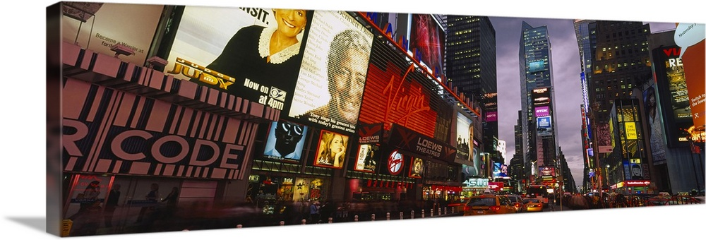 Large Solid-Faced Canvas Print Wall Art Print 48 x 16 entitled Buildings lit up at night, Times Square, Manhattan, New Yor... Solid-Faced Canvas Print entitled Buildings lit up at night, Times Square, Manhattan, New York City, New York State.  This wall hanging for a home or office is a panoramic photograph taken at street level of the enormous advertisements and buildings of this metropolitan avenue at twilight.  Multiple sizes available.  Primary colors within this image include Dark Red, Dark Yellow, Black, White.  Made in USA.  Satisfaction guaranteed.  Archival-quality UV-resistant inks.  Canvas depth is 1.25 and includes a finished backing with pre-installed hanging hardware.  Archival inks prevent fading and preserve as much fine detail as possible with no over-saturation or color shifting.