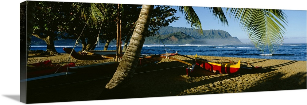 Large Solid-Faced Canvas Print Wall Art Print 48 x 16 entitled Catamaran on the beach, Hanalei Bay, Kauai, Hawaii Solid-Faced Canvas Print entitled Catamaran on the beach, Hanalei Bay, Kauai, Hawaii.  A large panoramic photograph of a boat on the beach that is mostly covered by the shadows of palm trees. Water and mountains can be seen in the background.  Multiple sizes available.  Primary colors within this image include Yellow, Dark Red, Brown, Black.  Made in USA.  All products come with a 365 day workmanship guarantee.  Archival-quality UV-resistant inks.  Canvas depth is 1.25 and includes a finished backing with pre-installed hanging hardware.  Archival inks prevent fading and preserve as much fine detail as possible with no over-saturation or color shifting.
