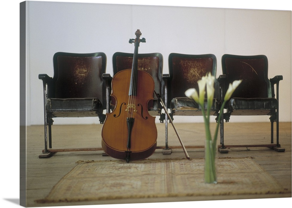 Large Solid-Faced Canvas Print Wall Art Print 30 x 20 entitled Cello leaning on attached chairs Solid-Faced Canvas Print entitled Cello leaning on attached chairs.  A cello stands on the floor and leans against a row of four seats. A vase of calla lilies sits on an area rug in front of the instrument.  Multiple sizes available.  Primary colors within this image include Dark Gray, Silver.  Made in the USA.  Satisfaction guaranteed.  Inks used are latex-based and designed to last.  Canvas depth is 1.25 and includes a finished backing with pre-installed hanging hardware.  Canvas is handcrafted and made-to-order in the United States using high quality artist-grade canvas.