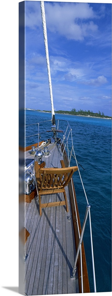 Large Solid-Faced Canvas Print Wall Art Print 16 x 48 entitled Chair on a boat deck, Exumas, Bahamas Solid-Faced Canvas Print entitled Chair on a boat deck, Exumas, Bahamas.  Multiple sizes available.  Primary colors within this image include Brown, Sky Blue, Gray, Dark Navy Blue.  Made in USA.  Satisfaction guaranteed.  Archival-quality UV-resistant inks.  Canvas depth is 1.25 and includes a finished backing with pre-installed hanging hardware.  Canvas is handcrafted and made-to-order in the United States using high quality artist-grade canvas.