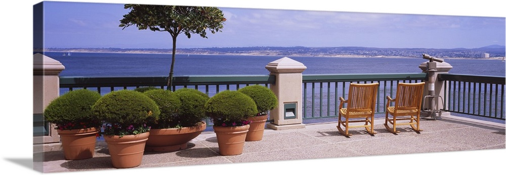 Large Solid-Faced Canvas Print Wall Art Print 48 x 16 entitled Chairs and potted plants on a deck, Monterey Bay, California Solid-Faced Canvas Print entitled Chairs and potted plants on a deck, Monterey Bay, California.  Multiple sizes available.  Primary colors within this image include Peach, Sky Blue, Dark Gray, Dark Forest Green.  Made in the USA.  All products come with a 365 day workmanship guarantee.  Archival-quality UV-resistant inks.  Featuring a proprietary design, our canvases produce the tightest corners without any bubbles, ripples, or bumps and will not warp or sag over time.  Canvas depth is 1.25 and includes a finished backing with pre-installed hanging hardware.