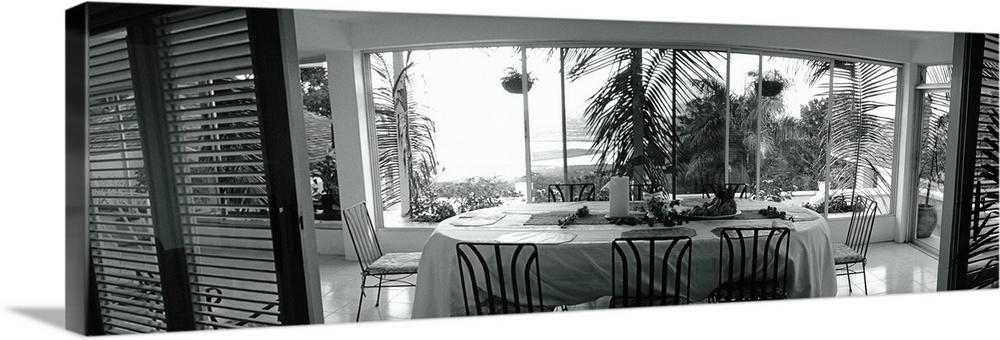 Large Solid-Faced Canvas Print Wall Art Print 48 x 16 entitled Chairs around a dining table, Montego Bay, Jamaica Solid-Faced Canvas Print entitled Chairs around a dining table, Montego Bay, Jamaica.  Multiple sizes available.  Primary colors within this image include Black, Gray, White.  Made in the USA.  All products come with a 365 day workmanship guarantee.  Archival-quality UV-resistant inks.  Archival inks prevent fading and preserve as much fine detail as possible with no over-saturation or color shifting.  Canvas is handcrafted and made-to-order in the United States using high quality artist-grade canvas.