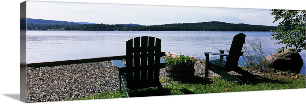 Large Solid-Faced Canvas Print Wall Art Print 48 x 16 entitled Chairs at the lakeside, Raquette Lake, Adirondack Mountains... Solid-Faced Canvas Print entitled Chairs at the lakeside, Raquette Lake, Adirondack Mountains, New York State,.  A panoramic photograph of Adirondack chairs arranged with a view of a lake on a bright sunny day.  Multiple sizes available.  Primary colors within this image include Black, Gray, White, Dark Forest Green.  Made in USA.  All products come with a 365 day workmanship guarantee.  Inks used are latex-based and designed to last.  Canvas is handcrafted and made-to-order in the United States using high quality artist-grade canvas.  Featuring a proprietary design, our canvases produce the tightest corners without any bubbles, ripples, or bumps and will not warp or sag over time.