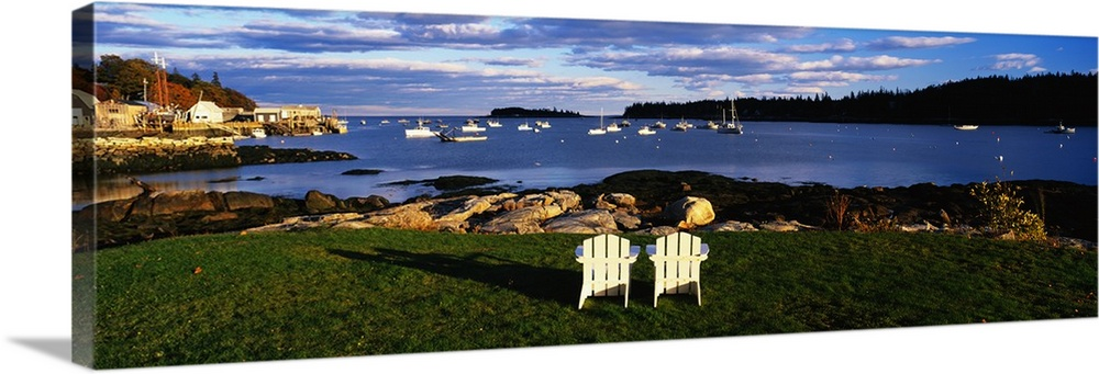 Large Solid-Faced Canvas Print Wall Art Print 48 x 16 entitled Chairs Lobster Village ME Solid-Faced Canvas Print entitled Chairs Lobster Village ME.  Giant, landscape photograph of two wooden chairs overlooking the coastline onto many boats in blue waters, in Lobster Village, Maine.  Multiple sizes available.  Primary colors within this image include Brown, Light Yellow, White, Dark Forest Green.  Made in the USA.  Satisfaction guaranteed.  Inks used are latex-based and designed to last.  Archival inks prevent fading and preserve as much fine detail as possible with no over-saturation or color shifting.  Featuring a proprietary design, our canvases produce the tightest corners without any bubbles, ripples, or bumps and will not warp or sag over time.