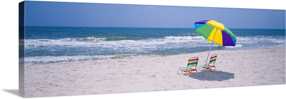 Large Solid-Faced Canvas Print Wall Art Print 48 x 16 entitled Chairs on the beach, Gulf of Mexico, Alabama Solid-Faced Canvas Print entitled Chairs on the beach, Gulf of Mexico, Alabama.  Panoramic photograph includes two chairs sitting under a vibrantly colored umbrella as the waves from the Gulf of Mexico hit against the sandy shores on a sunny day.  Multiple sizes available.  Primary colors within this image include Yellow, Blue, Silver, Royal Blue.  Made in the USA.  Satisfaction guaranteed.  Inks used are latex-based and designed to last.  Canvas depth is 1.25 and includes a finished backing with pre-installed hanging hardware.  Canvas is handcrafted and made-to-order in the United States using high quality artist-grade canvas.