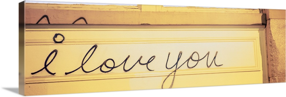 Large Solid-Faced Canvas Print Wall Art Print 48 x 16 entitled Close-up of I love you written on a wall Solid-Faced Canvas Print entitled Close-up of I love you written on a wall.  Multiple sizes available.  Primary colors within this image include Peach, Light Yellow, Black, White.  Made in USA.  All products come with a 365 day workmanship guarantee.  Archival-quality UV-resistant inks.  Archival inks prevent fading and preserve as much fine detail as possible with no over-saturation or color shifting.  Canvas depth is 1.25 and includes a finished backing with pre-installed hanging hardware.