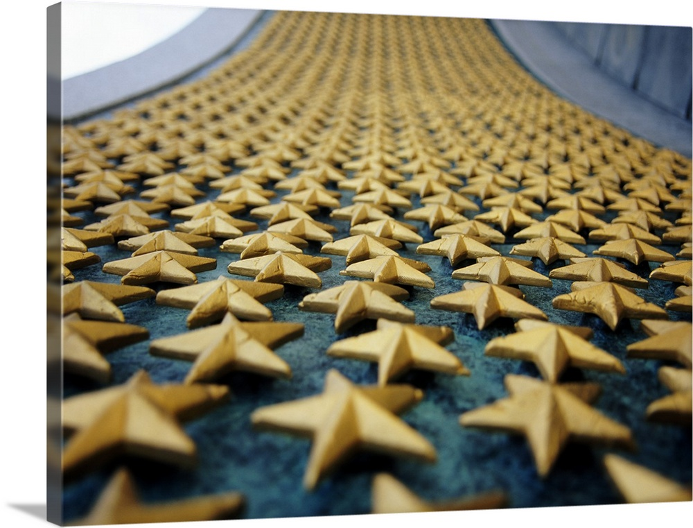 Large Solid-Faced Canvas Print Wall Art Print 48 x 36 entitled Close-up of stars mounted on the wall at a war memorial, Fr... Solid-Faced Canvas Print entitled Close-up of stars mounted on the wall at a war memorial, Freedom Wall, National World War II Memorial, Washington DC.  Small golden stars are attached onto a large wall at a war memorial in the countries capital.  Multiple sizes available.  Primary colors within this image include Peach, White, Dark Forest Green, Gray Blue.  Made in the USA.  All products come with a 365 day workmanship guarantee.  Archival-quality UV-resistant inks.  Canvas depth is 1.25 and includes a finished backing with pre-installed hanging hardware.  Canvas is handcrafted and made-to-order in the United States using high quality artist-grade canvas.