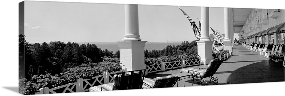 Large Solid-Faced Canvas Print Wall Art Print 48 x 16 entitled Deck chairs on a hotels porch, Grand Hotel, Mackinac Island... Solid-Faced Canvas Print entitled Deck chairs on a hotels porch, Grand Hotel, Mackinac Island, Michigan.  Giant landscape photograph looking down the outdoor balcony of the Grand Hotel as it overlooks the tree tops on Mackinac Island, Michigan.  Multiple sizes available.  Primary colors within this image include Black, Gray, Silver.  Made in the USA.  Satisfaction guaranteed.  Archival-quality UV-resistant inks.  Featuring a proprietary design, our canvases produce the tightest corners without any bubbles, ripples, or bumps and will not warp or sag over time.  Archival inks prevent fading and preserve as much fine detail as possible with no over-saturation or color shifting.