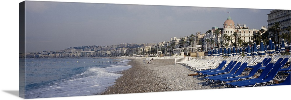Large Solid-Faced Canvas Print Wall Art Print 48 x 16 entitled Empty lounge chairs on the beach, Nice, French Riviera, France Solid-Faced Canvas Print entitled Empty lounge chairs on the beach, Nice, French Riviera, France.  Multiple sizes available.  Primary colors within this image include Dark Blue, Black, Light Gray, Dark Forest Green.  Made in USA.  All products come with a 365 day workmanship guarantee.  Archival-quality UV-resistant inks.  Canvas is handcrafted and made-to-order in the United States using high quality artist-grade canvas.  Canvas depth is 1.25 and includes a finished backing with pre-installed hanging hardware.
