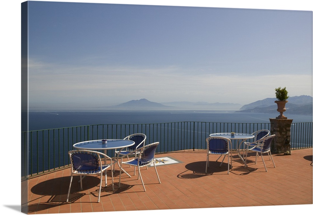 Large Solid-Faced Canvas Print Wall Art Print 30 x 20 entitled Empty tables and chairs on the balcony of a hotel, Ceasar A... Solid-Faced Canvas Print entitled Empty tables and chairs on the balcony of a hotel, Ceasar Augustus Hotel, Anacapri, Capri, Bay Of Naples, Campania, Italy.  Multiple sizes available.  Primary colors within this image include Brown, Dark Navy Blue, Light Gray Blue.  Made in USA.  Satisfaction guaranteed.  Inks used are latex-based and designed to last.  Canvas is handcrafted and made-to-order in the United States using high quality artist-grade canvas.  Archival inks prevent fading and preserve as much fine detail as possible with no over-saturation or color shifting.