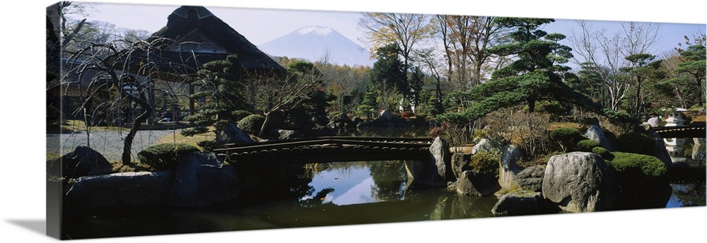 Large Solid-Faced Canvas Print Wall Art Print 48 x 16 entitled Footbridge in a garden, Japanese garden, Oshino, Japan Solid-Faced Canvas Print entitled Footbridge in a garden, Japanese garden, Oshino, Japan.  Multiple sizes available.  Primary colors within this image include Black, Light Gray, Muted Blue, Pale Blue.  Made in USA.  Satisfaction guaranteed.  Inks used are latex-based and designed to last.  Canvas is handcrafted and made-to-order in the United States using high quality artist-grade canvas.  Archival inks prevent fading and preserve as much fine detail as possible with no over-saturation or color shifting.