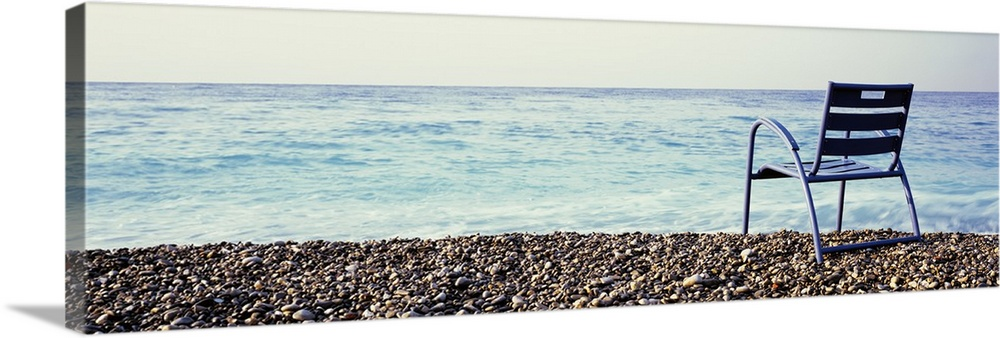 Large Solid-Faced Canvas Print Wall Art Print 48 x 16 entitled France, Cote de Azur, Nice, Vacant chair on the beach Solid-Faced Canvas Print entitled France, Cote de Azur, Nice, Vacant chair on the beach.  Multiple sizes available.  Primary colors within this image include Black, Gray, White, Muted Blue.  Made in the USA.  All products come with a 365 day workmanship guarantee.  Archival-quality UV-resistant inks.  Featuring a proprietary design, our canvases produce the tightest corners without any bubbles, ripples, or bumps and will not warp or sag over time.  Canvas is handcrafted and made-to-order in the United States using high quality artist-grade canvas.