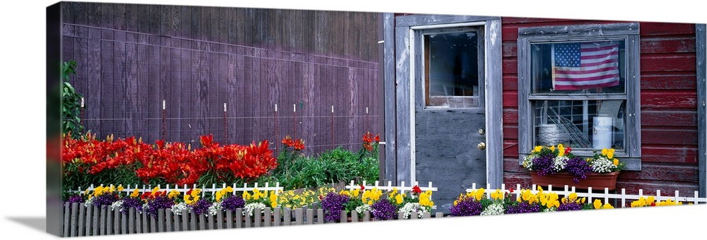 Large Solid-Faced Canvas Print Wall Art Print 48 x 16 entitled Garden in front of a house, Main Street, Haines, Alaska Solid-Faced Canvas Print entitled Garden in front of a house, Main Street, Haines, Alaska.  Multiple sizes available.  Primary colors within this image include Red, Dark Red, Light Yellow, Black.  Made in the USA.  Satisfaction guaranteed.  Inks used are latex-based and designed to last.  Canvas is handcrafted and made-to-order in the United States using high quality artist-grade canvas.  Canvas depth is 1.25 and includes a finished backing with pre-installed hanging hardware.
