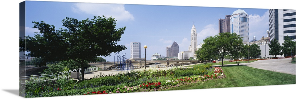 Large Solid-Faced Canvas Print Wall Art Print 48 x 16 entitled Garden in front of skyscrapers in a city, Scioto River, Col... Solid-Faced Canvas Print entitled Garden in front of skyscrapers in a city, Scioto River, Columbus, Ohio.  Multiple sizes available.  Primary colors within this image include Forest Green, Sky Blue, Black, Silver.  Made in USA.  All products come with a 365 day workmanship guarantee.  Archival-quality UV-resistant inks.  Archival inks prevent fading and preserve as much fine detail as possible with no over-saturation or color shifting.  Featuring a proprietary design, our canvases produce the tightest corners without any bubbles, ripples, or bumps and will not warp or sag over time.