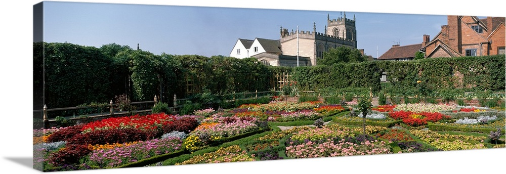 Large Solid-Faced Canvas Print Wall Art Print 48 x 16 entitled Gardens at Stratford upon Avon England Solid-Faced Canvas Print entitled Gardens at Stratford upon Avon England.  Multiple sizes available.  Primary colors within this image include Dark Red, Black, White, Dark Forest Green.  Made in USA.  All products come with a 365 day workmanship guarantee.  Inks used are latex-based and designed to last.  Archival inks prevent fading and preserve as much fine detail as possible with no over-saturation or color shifting.  Canvas is handcrafted and made-to-order in the United States using high quality artist-grade canvas.