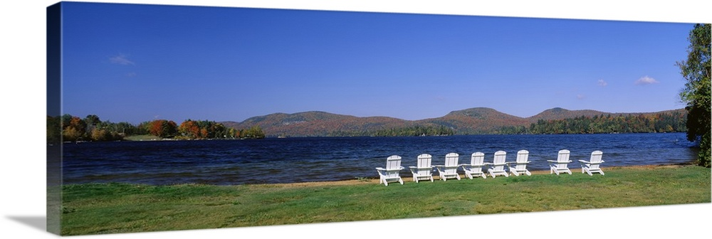Large Solid-Faced Canvas Print Wall Art Print 48 x 16 entitled Group of lounge chairs near a lake, Blue Mountain Lake, New... Solid-Faced Canvas Print entitled Group of lounge chairs near a lake, Blue Mountain Lake, New York State.  Multiple sizes available.  Primary colors within this image include Dark Yellow, Dark Forest Green, Royal Blue, Dark Navy Blue.  Made in USA.  All products come with a 365 day workmanship guarantee.  Archival-quality UV-resistant inks.  Archival inks prevent fading and preserve as much fine detail as possible with no over-saturation or color shifting.  Featuring a proprietary design, our canvases produce the tightest corners without any bubbles, ripples, or bumps and will not warp or sag over time.
