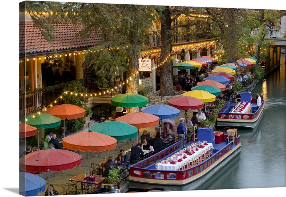 Large Gallery-Wrapped Canvas Wall Art Print 24 x 16 entitled Group of people in a restaurant along a river, San Antonio Ri... Gallery-Wrapped Canvas entitled Group of people in a restaurant along a river, San Antonio River, San Antonio, Texas.  Large photo on canvas of colored umbrellas along a waterfront with boats with tables and chairs docked next to them.  Multiple sizes available.  Primary colors within this image include Yellow, Brown, Black, White.  Made in USA.  Satisfaction guaranteed.  Inks used are latex-based and designed to last.  Canvas frames are built with farmed or reclaimed domestic pine or poplar wood.  Canvas is designed to prevent fading.