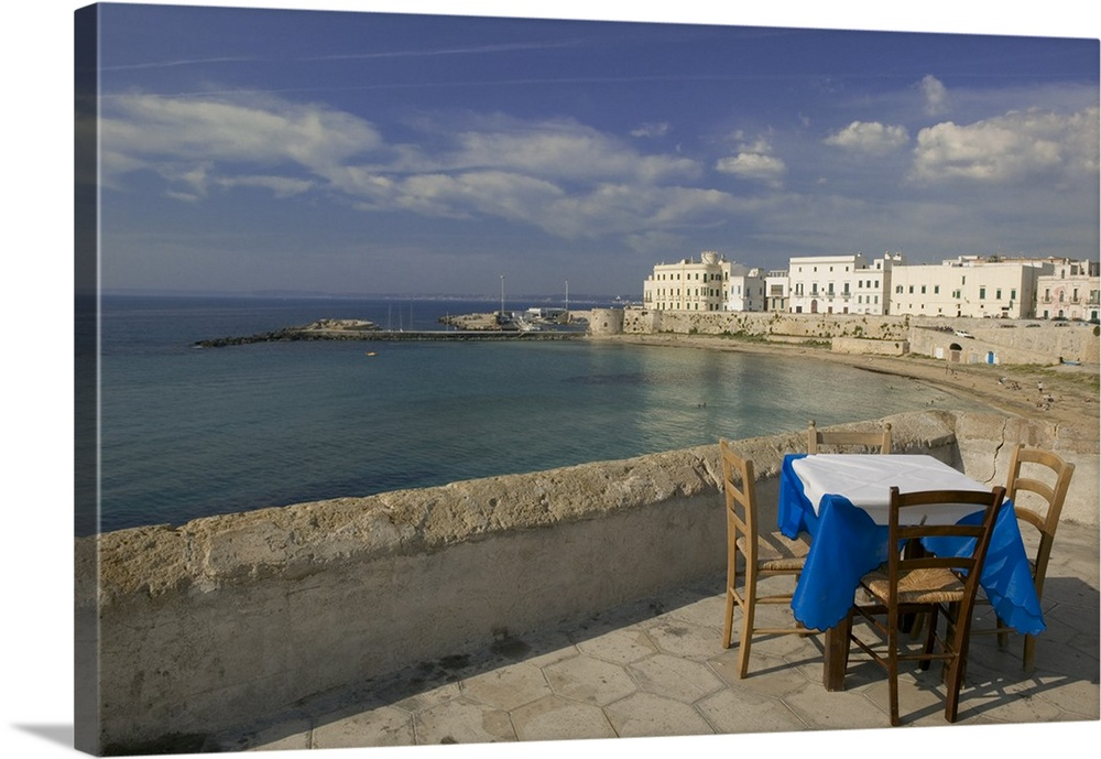 Large Solid-Faced Canvas Print Wall Art Print 30 x 20 entitled High angle view of a table and a chair in a cafe, Gallipoli... Solid-Faced Canvas Print entitled High angle view of a table and a chair in a cafe, Gallipoli, Apulia, Italy.  Photograph of table and chairs near waters edge with buildings in the distance under a cloudy sky.  Multiple sizes available.  Primary colors within this image include Black, Light Gray, Dark Navy Blue.  Made in USA.  Satisfaction guaranteed.  Inks used are latex-based and designed to last.  Canvas depth is 1.25 and includes a finished backing with pre-installed hanging hardware.  Featuring a proprietary design, our canvases produce the tightest corners without any bubbles, ripples, or bumps and will not warp or sag over time.