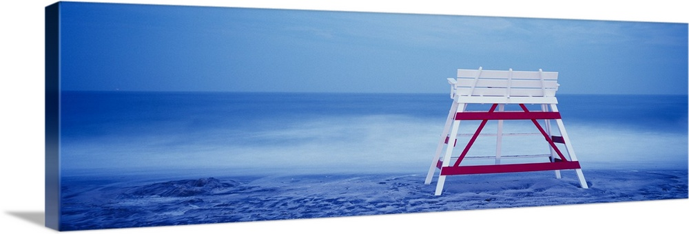 Large Solid-Faced Canvas Print Wall Art Print 48 x 16 entitled Lifeguard chair on the beach, Cape May, New Jersey Solid-Faced Canvas Print entitled Lifeguard chair on the beach, Cape May, New Jersey.  Panoramic photograph on a big canvas of the back of an empty, wooden lifeguard chair sitting on the beach in front of blue waters in Cape May, New Jersey.  Multiple sizes available.  Primary colors within this image include Plum, Sky Blue, Black, Royal Blue.  Made in the USA.  Satisfaction guaranteed.  Inks used are latex-based and designed to last.  Canvas is handcrafted and made-to-order in the United States using high quality artist-grade canvas.  Archival inks prevent fading and preserve as much fine detail as possible with no over-saturation or color shifting.