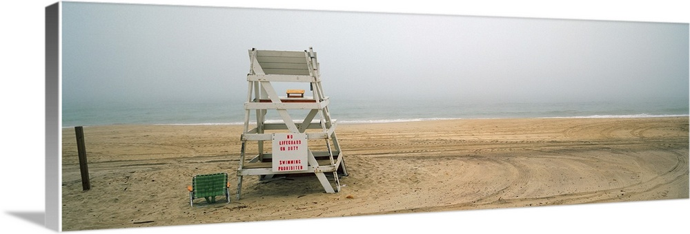 Large Solid-Faced Canvas Print Wall Art Print 48 x 16 entitled Lifeguard chair on the beach, Montauk, New York State Solid-Faced Canvas Print entitled Lifeguard chair on the beach, Montauk, New York State.  Multiple sizes available.  Primary colors within this image include Black, Gray, Silver.  Made in the USA.  All products come with a 365 day workmanship guarantee.  Archival-quality UV-resistant inks.  Featuring a proprietary design, our canvases produce the tightest corners without any bubbles, ripples, or bumps and will not warp or sag over time.  Canvas depth is 1.25 and includes a finished backing with pre-installed hanging hardware.