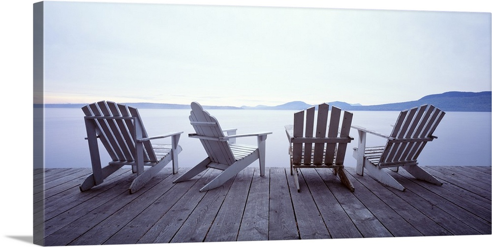 Large Gallery-Wrapped Canvas Wall Art Print 24 x 12 entitled Lounge Chairs Moosehead Lake ME Gallery-Wrapped Canvas entitled Lounge Chairs Moosehead Lake ME.  Adirondack chair art of four chairs at the edge of a dock on a misty lake in summer.  Multiple sizes available.  Primary colors within this image include White, Muted Blue.  Made in USA.  Satisfaction guaranteed.  Inks used are latex-based and designed to last.  Canvas is acid-free and 20 millimeters thick.  Canvas is designed to prevent fading.