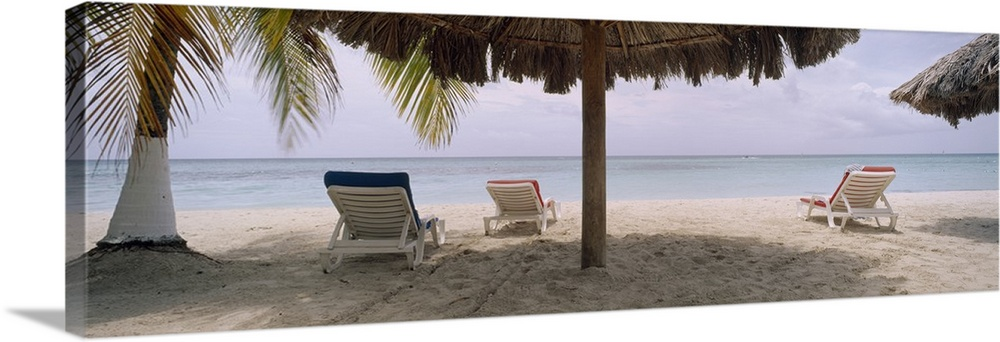 Large Solid-Faced Canvas Print Wall Art Print 48 x 16 entitled Lounge chairs on 7-Mile Beach, Negril, Jamaica Solid-Faced Canvas Print entitled Lounge chairs on 7-Mile Beach, Negril, Jamaica.  Huge, wide angle photograph of several lounge chairs beneath umbrellas and a palm tree, on 7-Mile Beach in Negril, Jamaica.  Multiple sizes available.  Primary colors within this image include Gray, Pale Blue, Dark Navy Blue.  Made in the USA.  All products come with a 365 day workmanship guarantee.  Archival-quality UV-resistant inks.  Canvas is handcrafted and made-to-order in the United States using high quality artist-grade canvas.  Archival inks prevent fading and preserve as much fine detail as possible with no over-saturation or color shifting.